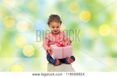 childhood, fashion, birthday, holidays and people concept - happy smiling little african american baby girl with gift box sitting on floor