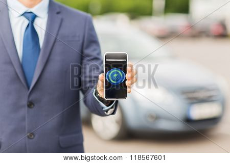 transport, business trip, ecology, technology and people concept - close up of man showing smartphone eco mode icon on screen on car parking