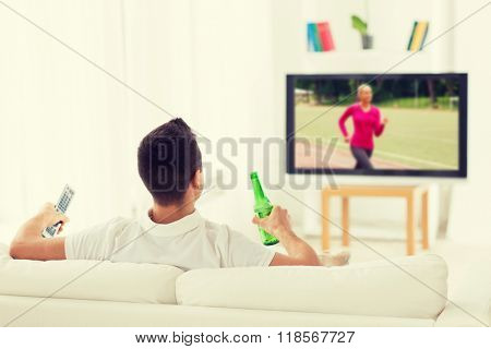 leisure, technology, mass media and people concept - man watching sport channel on tv and drinking bottle beer at home from back