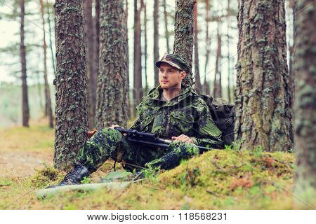hunting, war, army and people concept - young soldier, ranger or hunter with gun and backpack resting in forest