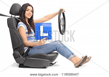 Young woman holding an L sign and a steering wheel seated on a car seat isolated on white background