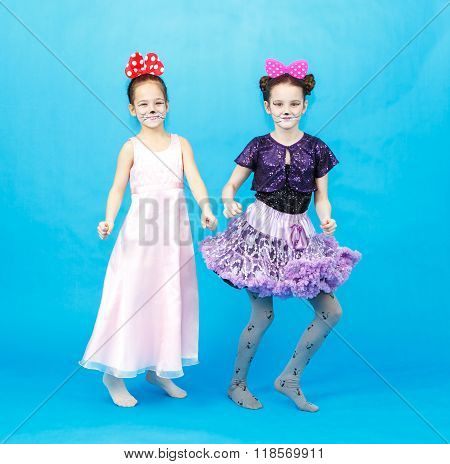 Two Smiling Funny Girls In Party Costumes Posing On Blue Background