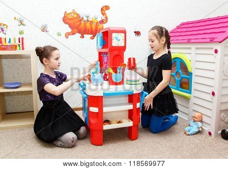 Two Little Girls Play Role Game With Toy Kitchen In Day Care Center