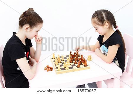 Two Cute Girls Play Chess. Black Rook Move.