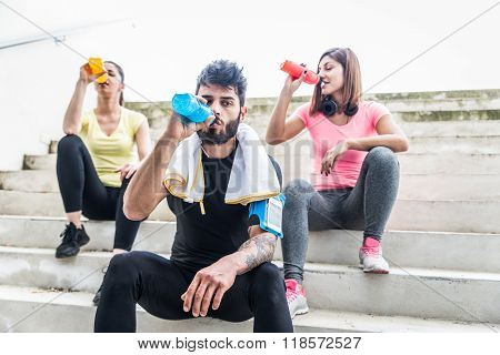 Joggers Having Rest And Drinking