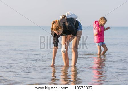 Woman With Child Walking Along The Beach And Collect Seashells