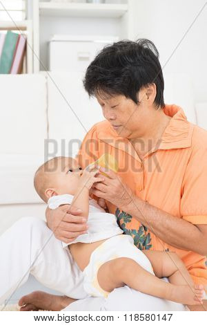 Grandmother taking care grandchild at home. Feeding solid food fruit puree with bottle.