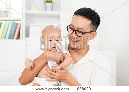 Asian family at home. Bad father giving cigarette to baby. Cigarette with lit and smoke. Unhealthy lifestyle or stop smoking concept photo.
