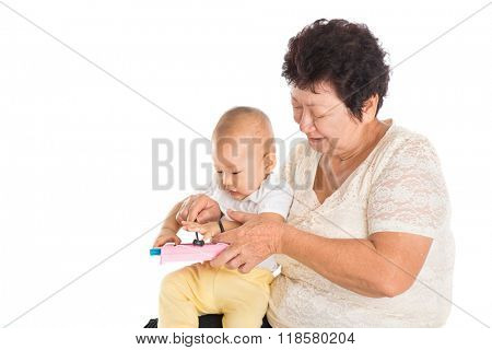 Grandmother and grandson playing musical instrument together, baby sound development concept,  isolated on white background.