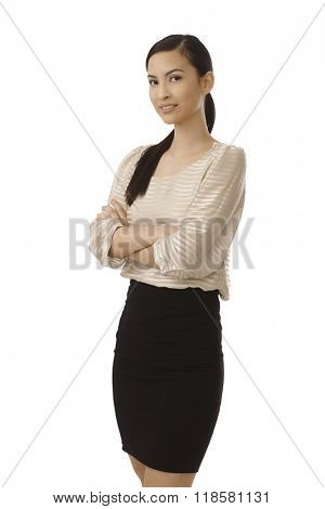 Young confident businesswoman standing arms crossed wearing mini skirt, smiling. i