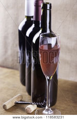 glass of rose wine, corkscrew on the background bottles