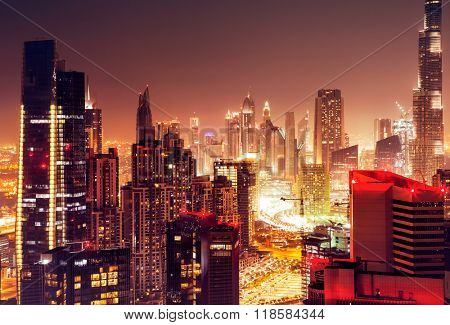 Dubai city at night, beautiful nighttime cityscape, modern tall skyscrapers glowing with many lights, luxury buildings in UAE