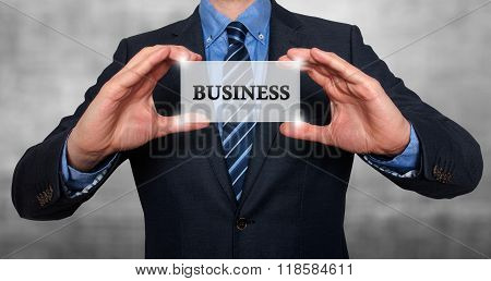 Businessman Holds White Card With Business Sign, Grey - Stock Photo