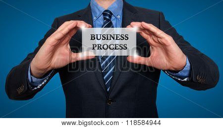 Businessman Holds White Card With Business Process Sign, Blue- Stock Photo