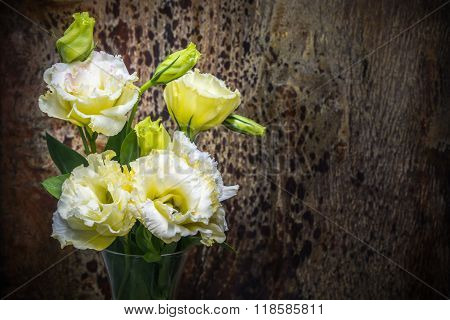 White Yellow Lisianthius Flower In Glass Jar Decorated On Dark Tone Wooden Texture