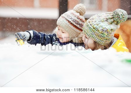 Mother with child play in snow on winter walk, positive emotions, outdoor. Snowfall, blizzard.