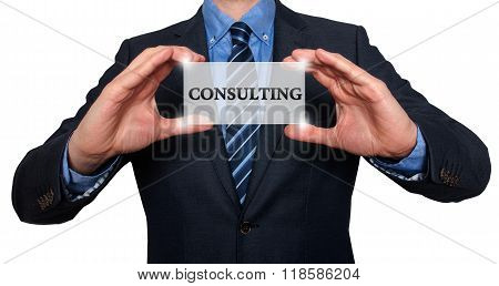 Businessman Holds White Card With Consulting Sign, White - Stock Photo