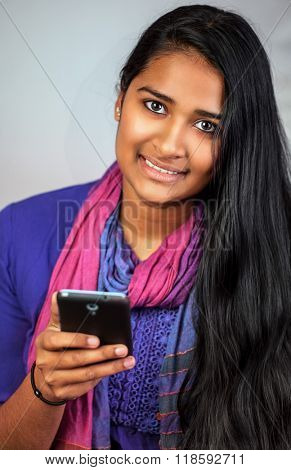 Young pretty india woman looking and smiling at camera with her smart-phone, vertical