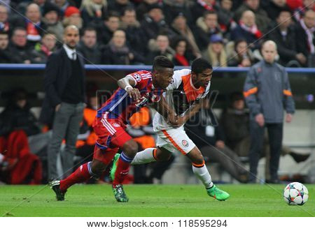 MUNICH, GERMANY - MARCH 11 2015: Bayern's manager Josep Guardiola looks on as Bayern Munich's David Alaba  and Shaktar's Douglas Costa compete for the ball during the UEFA Champions League match