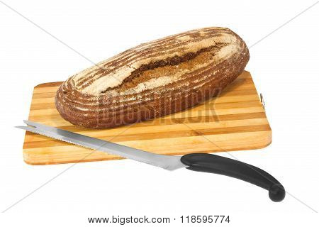 Loaf Of Rye Bread On A Wooden Board With A Knife