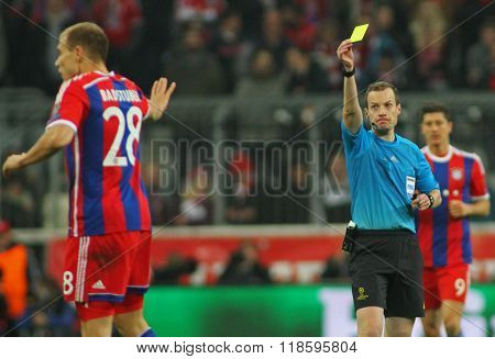 MUNICH, GERMANY - MARCH 11 2015:  Referee William Collum shows a yellow card to Bayern Munich's defender Holger Badstuber  during the UEFA Champions League match