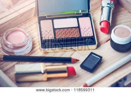Set of nude and pink eyeshadows, coral lipsticks and eyeliner for natural makeup