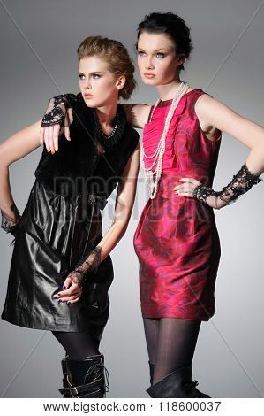 young stylish two model in coat dress posing in the studio