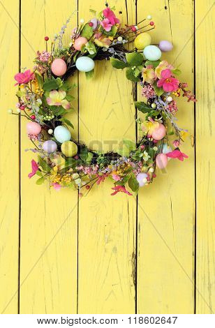 Easter egg wreath on a yellow wooden background.