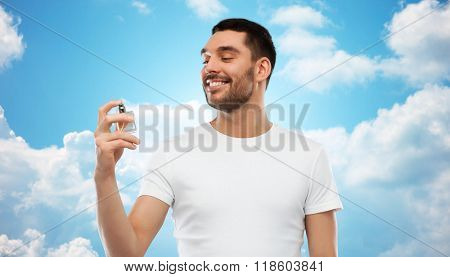 perfumery, beauty and people concept - happy smiling young man with male perfume over blue sky and clouds background