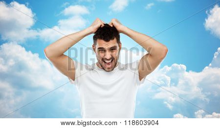 emotions, stress, madness and people concept - crazy shouting man rending ones hair in t-shirt over blue sky and clouds background