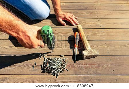 Worker using joiner tools outdoor - Closeup young professional man working with green materials - Concept of hard work craft