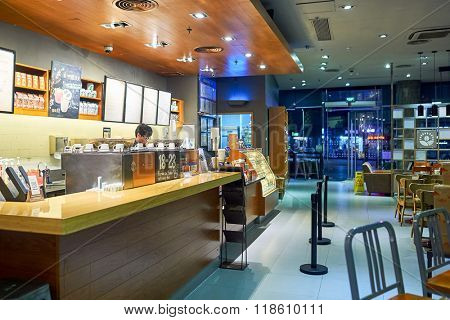 SHENZHEN, CHINA - JANUARY 31, 2015: Starbucks Cafe interior at night. Starbucks Corporation is an American global coffee company and coffeehouse chain based in Seattle, Washington