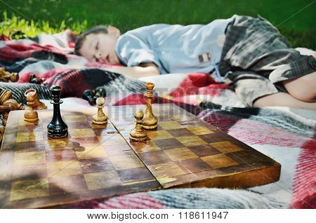 Tired Boy Fell Asleep After A Game Of Chess. Focus On Chess Figures