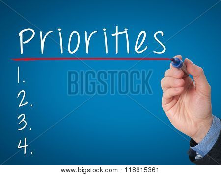 Business Man Hand Writing Priorities List With Marker Isolated On Blue