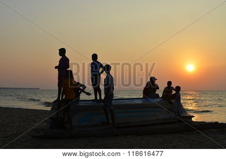 Sri-Lanka, Negombo, January 10, 2016-Boys on the flipped over boat on the beach. Sunset. Backlight