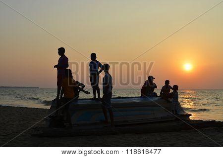 Sri-Lanka, Negombo, January 10, 2016-Boys on the flipped over boat on the beach. Sunset. Backlight