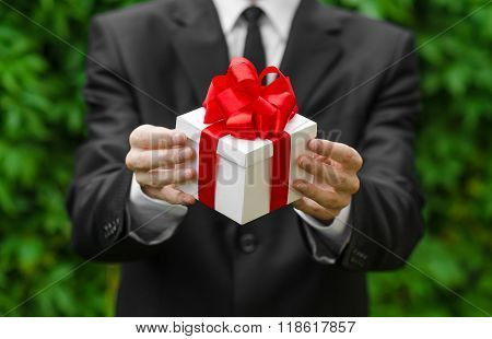 Gift And Business Theme: A Man In A Black Suit Holding A Gift In A White Box With A Red Ribbon On A
