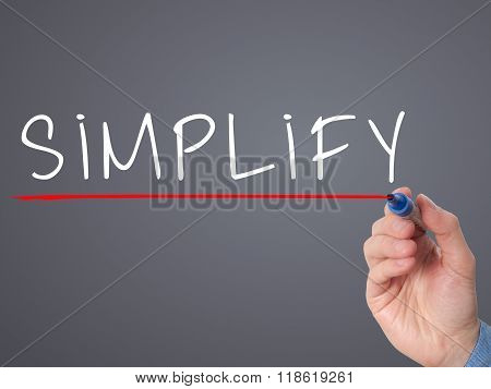 Businessman Hand Writing Simplify With Marker On Transparent Wipe Board Isolated On Grey
