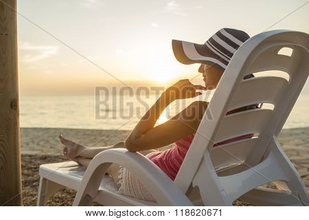 Young Woman With Sunhat Sitting On A Plastic Beach Chair