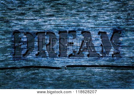 Word Dream Carved In The Blue Colored Old Cracked With And Grunge Look