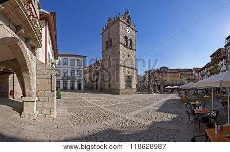 Guimaraes, Portugal - October, 2015: People enjoying the esplanades in the Oliveira Square with the Nossa Senhora da Oliveira Church, Salado Monument and old Town-Hall. UNESCO World Heritage Site.