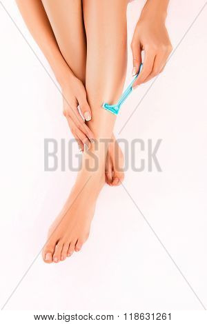 Top View Close Up Photo Of Young  Woman Shaving Her Leg