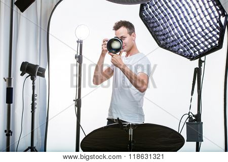 Young pro photographer with digital camera - DSLR and a huge telephoto lens in her well equiped studio, taking photos (color toned image; shallow DOF)