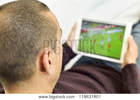 a young man lying on the couch watches a soccer match in streaming in his tablet computer