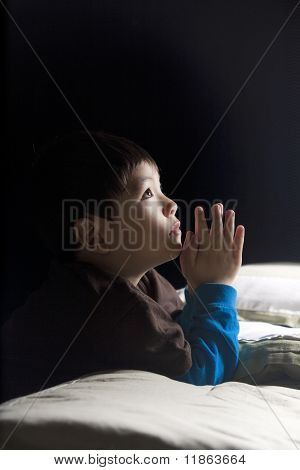 Boy saying his prayers.