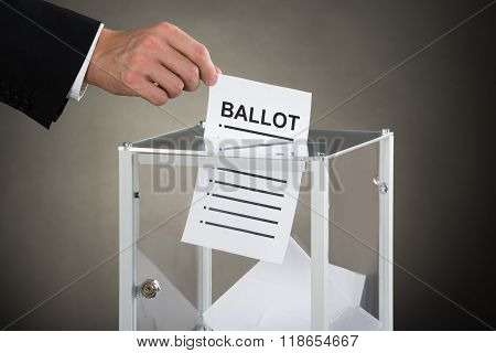 Businessperson Hand Putting Ballot In Glass Box