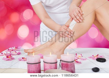 Beautician Waxing Woman's Leg In Beauty Salon