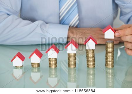 Businessman With House Model On Stacked Coins