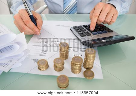 Businessman Calculating Invoice With Coins At Desk