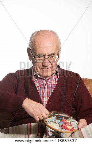 Senior Man Cross-stitching